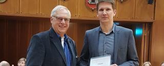 Dr. Ulrich Kumme überreicht Stefan Fischer das Zertifikat für das Gütesiegel.