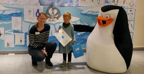 """Die vierjährige Nele gewann mit ihrem Namensvorschlag """"Pepe"""" und ihrem Pinguin-Bild den Wettbewerb und nahm dafür von Karen Thiele, Kaufmännische Leiterin am BK, den ersten Preis entgegen."""